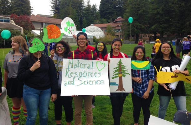 Students holding signs promoting natural resources and science