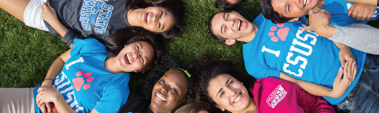 diverse students laying on grass